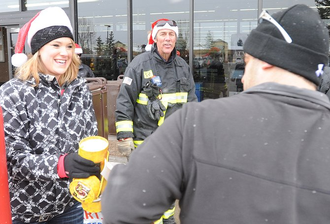 Audre Torgerson accepts a donation in front of Walmart on Sunday afternoon as a part of Routt County United Way's annual Holiday Wishes program, which uses gift donations to help local families in need fill their holiday wish lists.