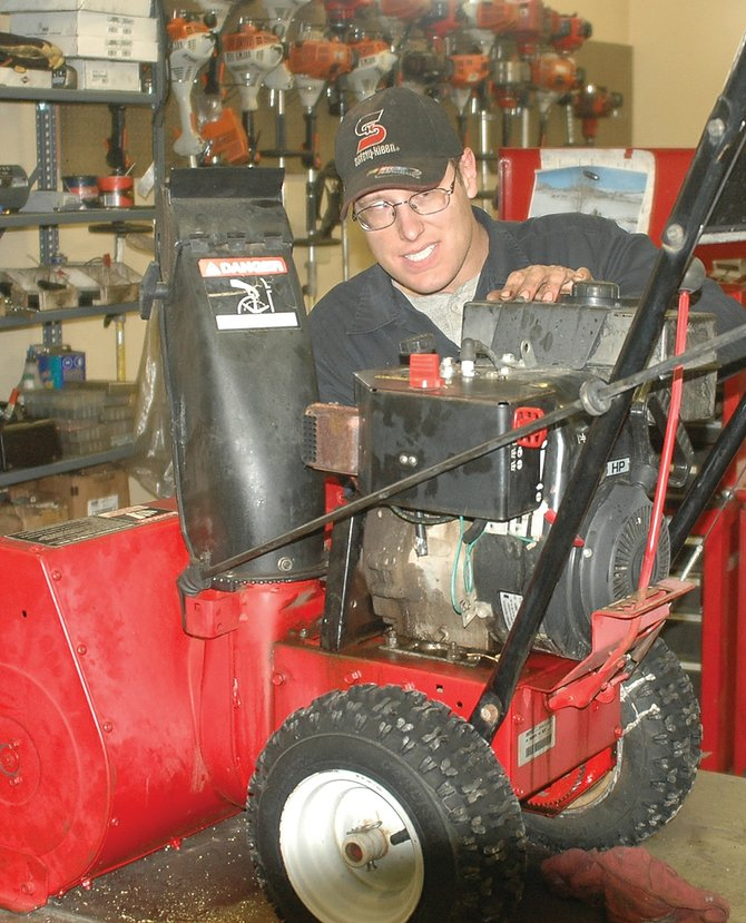 Justin Haynes, of Precision Sharpening and Repair Service, works on repairing a Snapper snowblower that had a run-in with a pole.