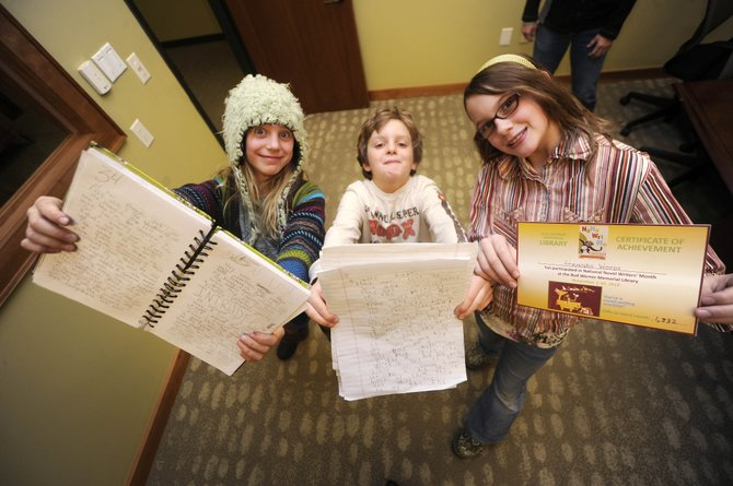 National Novel Writing Month's Young Writers Program participants, from left, Delaney Ziegman, Max Hall, and Hannah Woods celebrated their writing accomplishments Wednesday at Bud Werner Memorial Library.