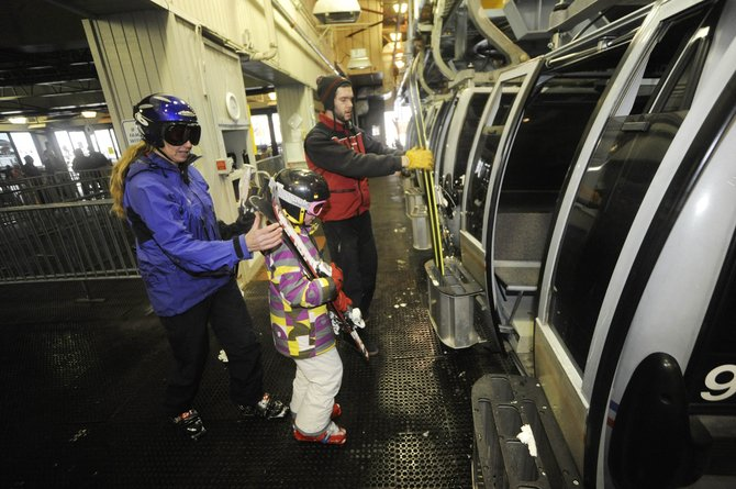 Steamboat Ski and Resort Corp. lift operator Kevin Reid helps Steamboat resident Kristy Fox and her nine-year-old daughter Lily load a gondola car Friday. Ski Corp. officials spent the day fielding phone calls about security measures.