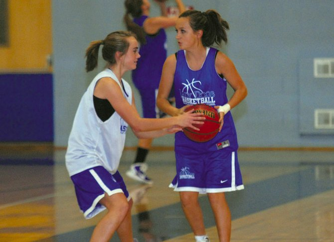 Moffat County High School seniors Maddy Jourgensen, left, and Nike Cleverly work on defensive drills during a practice session. Both girls are on the MCHS varsity girls basketball team. The team lost, 38-35, in its Friday game against Evanston, Wyo., at the Shanon Johnson Tournament hosted by Uintah High School.