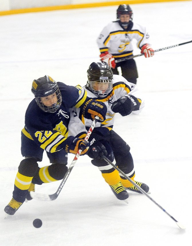Steamboat's Matthew Theielemann tangles with an Arapahoe defender on Sunday during the Pee Wee A championship of the Ski Town Classic at Howelsen Ice Arena in Steamboat Springs. Steamboat won the match up, 2-1.