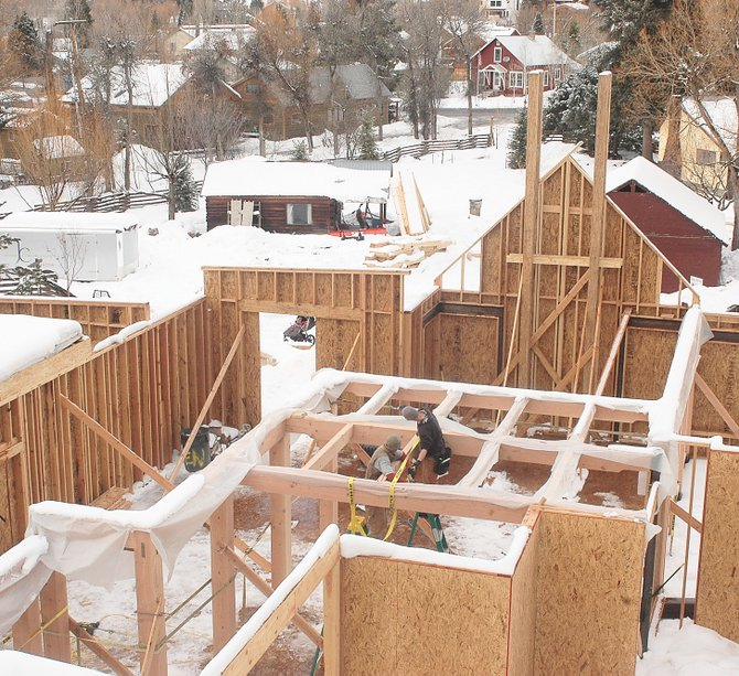 Carpenters work through the December snow at the site of a new single-family home at the east end of Spruce Street in Old Town. Jessen Construction and Brooks Design Build are collaborating on the project.