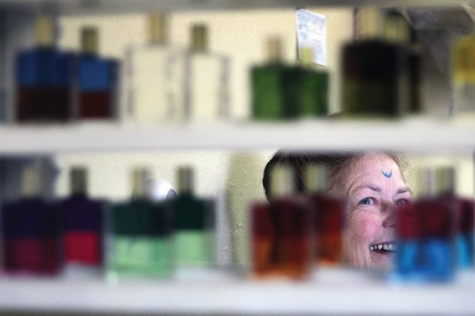 Craig resident Sharon Miller, 66, is reflected Thursday in a mirror display of bottles of color therapy, which is an oil and water mixture and serves as part of soul readings that Miller provides as part of her work at the store. Miller opened her store, Crystal Sanctuary, Nov. 26 and said business has been good.