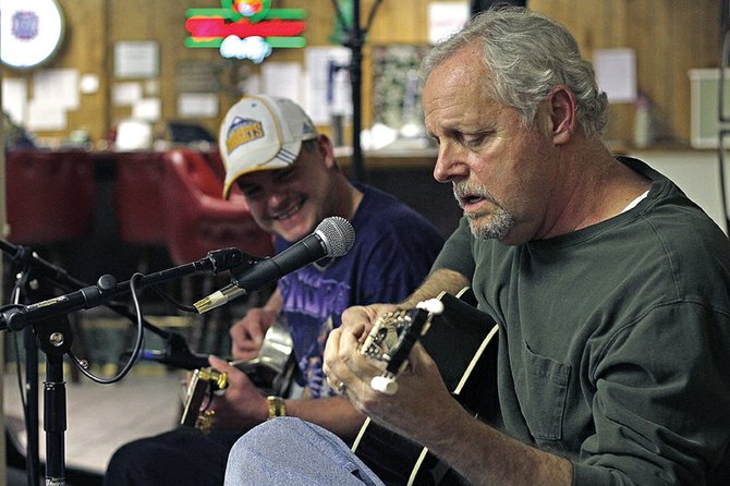 "Stephen Ghirardelli, right and his son Brian, left, play the song ""Key to the Highway"" by Big Bill Broonzy on Dec. 3 during an open mic night at the Veterans of Foreign Wars Post 4265. Brian and Stephen share a passion for the blues and played together in a blues and rock cover band called The Blue Rooster Band for about 10 years."
