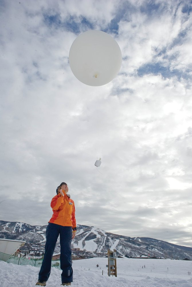Linda Danter, a volunteer for the Storm Peak Laboratory Cloud Property Validation Experiment, releases a weather balloon from a research site near Yampa Valley Medical Center. The balloon sends information back to the scientists who are gathering information for an extended study of clouds from sites at different elevations on the mountain and the site on the valley floor.