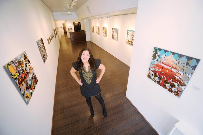 K. Saari Gallery owner Kimberly Saari stands among the digital contemporary works of artist Kathryn Dunlevie. The work will be on display through Jan. 2.