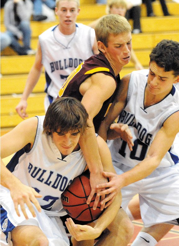 Moffat County seniors Chet Harvey, left, and Zach Raftopoulos wrestle for the ball against a Windsor player during the boys varsity basketball team's game at the Steamboat Springs Shoot-Out. The team lost in its Thursday game against Rifle, 73-56, in the first round of the Palisade Tournament.