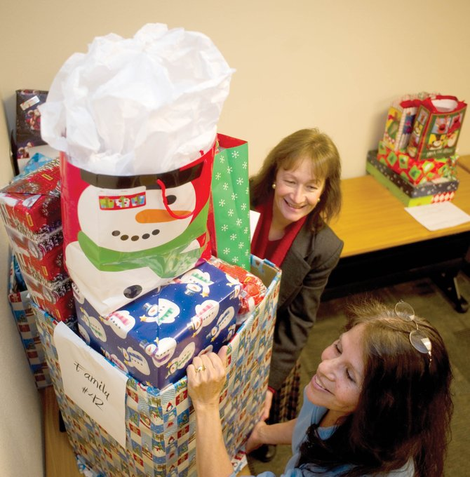 Vickie Clark and Adele Heilner, of Routt County Department of Human Ser­­vices, move a package that is part of the United Way's Holiday Wishes program. The program delivers presents and other holiday items to families in need in Routt County.