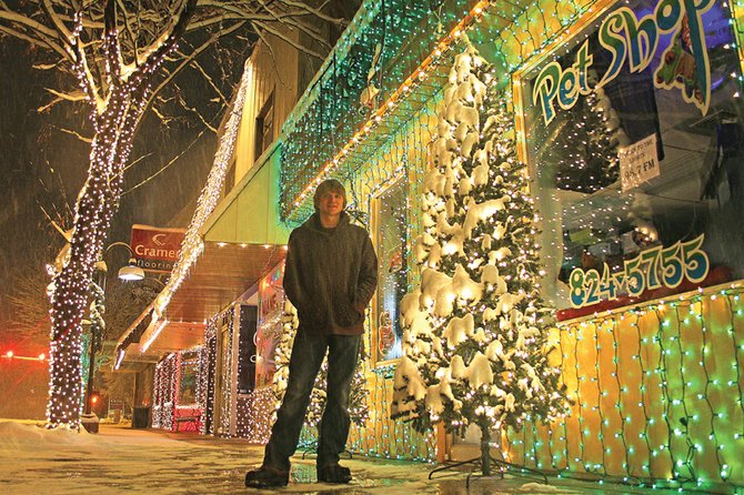 Clint Gabbert, 19, stands Monday in front of a Christmas lights and music display in downtown Craig. He is shown outside his pet store, The Jungle, which he has owned since March. Gabbert said his downtown light show contains 30,000 lights, and the one he organized at his parents' home north of Craig has about 70,000 lights.