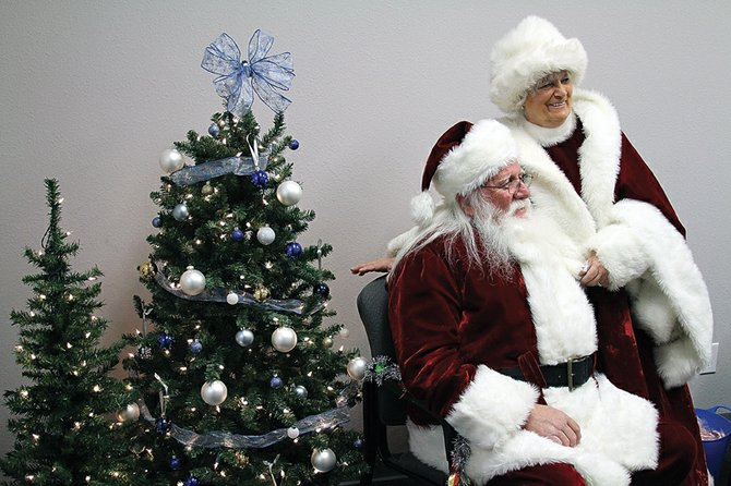 Santa and Mrs. Claus await the arrival of children at the Craig Daily Press offices Friday. About 150 area children submitted their letters to Santa through the Daily Press.