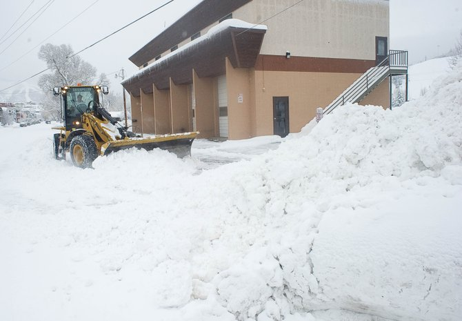 A city plow truck clears snow from in front of the Routt County Search and Rescue barn in downtown Steamboat Springs on Tuesday.
