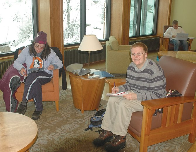 Horizons Specialized Services clients Misty Garcia, left, and Jeffrey Turner catch up on their reading and journal writing Tuesday at Bud Werner Memorial Library.