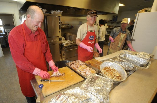 Volunteers, from left, Ray Wright, Larry Handing and Mitch Clementson carve turkey and ham during Saturday's Steamboat Springs Board of Realtors Community Christmas Dinner at the Steamboat Springs Community Center.