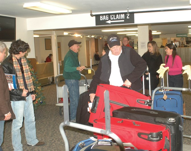 Retired Moffat County school teachers and skycaps Ken Harjes and Don Riley help arriving passengers at Yampa Valley Regional Airport with their bags Monday.