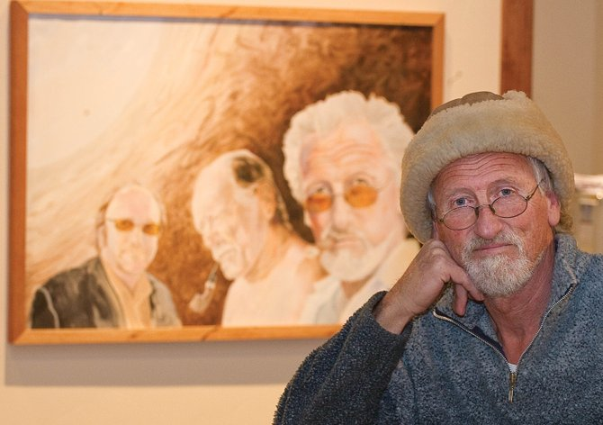 Sigi Malinowski, a former Steamboat Springs resident, sits in front of a self-portrait, which will be on display at The Olympian Sales Center. Malinowski will show his work at the sales center starting today and continuing through January.