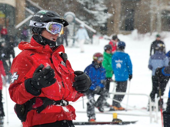 Duncan Draper, who works for courtesy patrol at Steamboat Ski Area, visits with skiers at the base of the ski area Wednesday. The courtesy patrol encourages skiers to obey rules and slow down in congested areas.