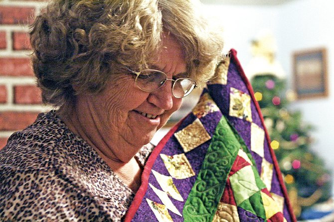 "Craig resident Linda Pinnt displays her latest quilt, ""Country Rose."" Pinnt is among eight finalists in a national quilting contest sponsored by McCall's Quilting magazine. Pinnt is asking local residents to vote for her work later this week at www.mccallsquilting.com."