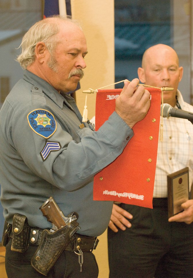 Hayden Police Department Sgt. Gordon Booco has been named acting chief of the town's Police Department. Booco takes over for Ray Birch, who accepted an offer from Routt County Sheriff-elect Garrett Wiggins to be his undersheriff. In this March 2009 photo, Booco presents Birch with a cloth scroll containing a collection of pins Hayden police officers wore while Birch served in Iraq.