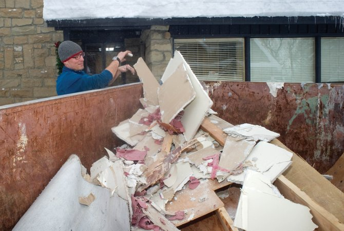 Matt McQueen dumps drywall into a Dumpster outside St. Paul's Episcopal Church on Wednesday. A broken water pipe Monday morning damaged the basement and the children's classroom.