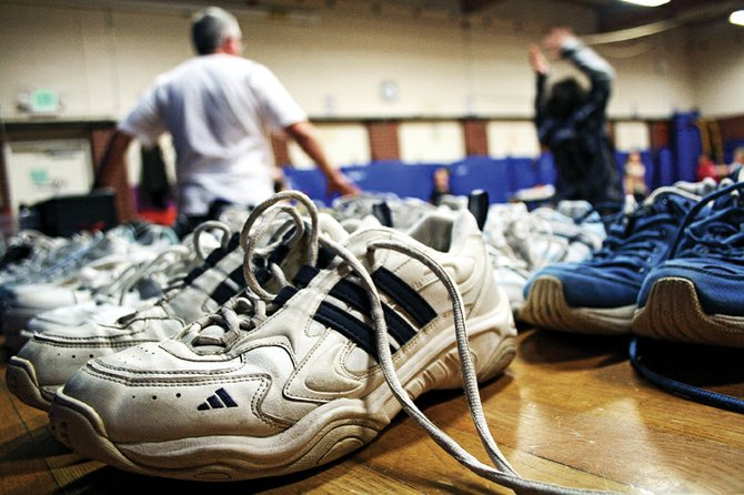 Rows of sneakers line the stage in the East Elementary School gymnasium. Physical education teacher Brett Sperl, shown in the background, has been collecting shoes for several years for his Renew-A-Shoe program, which provides sneakers to children who need them.