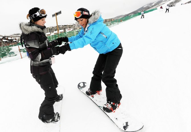 Katie Mason, left, helps Emily Clay down the Preview run at Steamboat Ski Area on Friday. Mason, an experienced snowboarder, said she was happy to offer her friend free lessons, even though anger and frustration often can get in the way during similar lessons to friends and loved ones. The key, they said, was about keeping things relaxed.