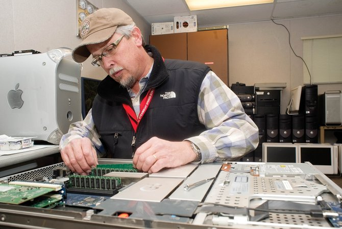 Senior Network Systems Engineer Dave Holloway works to refurbish a piece of computer equipment at Strawberry Park Elementary School on Tuesday afternoon.  The Steamboat Springs School District is asking for $900,000 in technology-related gifts from the Education Fund Board.