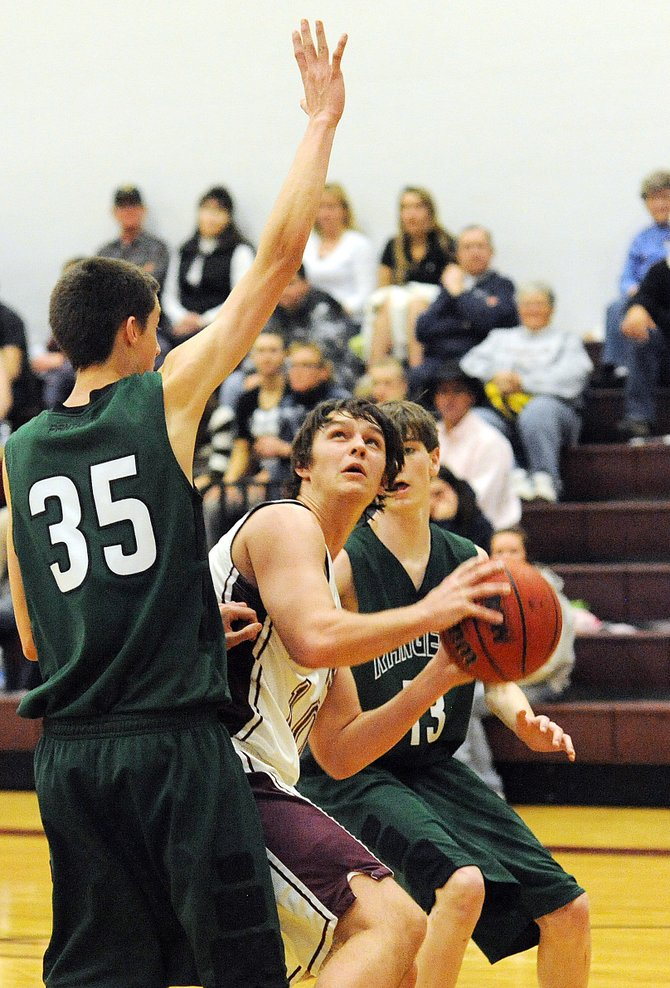 Soroco High School's Ben Strait has no where to go as he's bracketed by Rangely defenders Friday night. The Rams lost the game, 72-58.