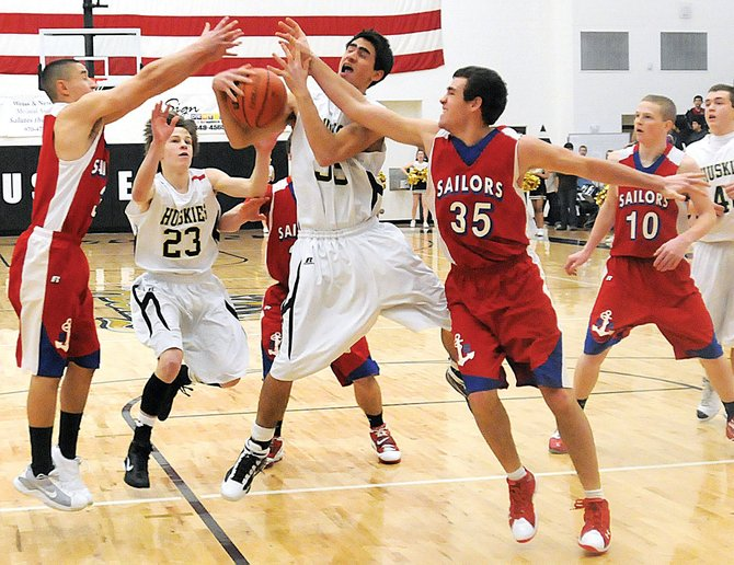 Battle Mountain's Joe Lybarger and Cody Hervert and Steamboat Springs' Eric Trousil battle for the ball Friday at Battle Mountain High School in Edwards. Steamboat Springs won, 53-32.