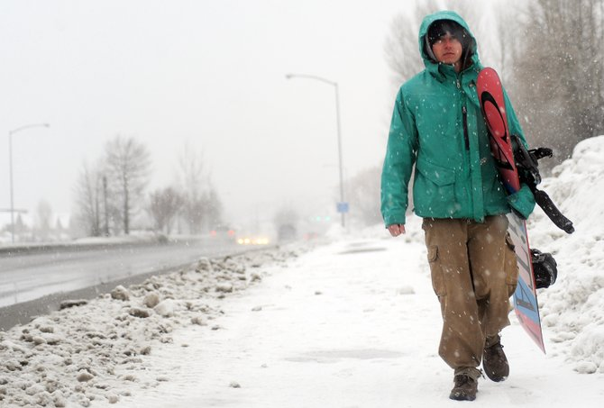 Tyler Sullenberger walks along U.S. Highway 40 on Sunday afternoon as a winter storm begins to unload snow in Steamboat Springs. A winter weather advisory and hazardous weather outlook has been issued for the Upper Yampa River Basin.