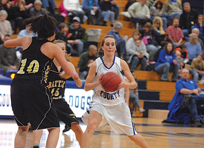 Maddy Jourgensen, a Moffat County High School senior, looks to pass with two Battle Mountain defenders applying pressure Saturday night at MCHS. The Bulldogs jumped to a 22-point first quarter lead and never backed down to win their second straight Western Slope League game, 59-29.