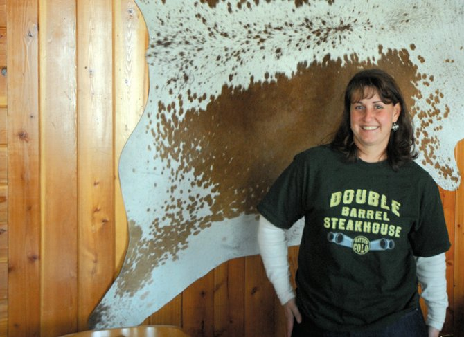 Ann Marie Roberts, the Moffat County High School girls golf coach, stands in the Double Barrel Steakhouse, a restaurant she runs with her husband, Pat. The game of golf has taken Roberts from Craig to Nebraska to Massachusetts before bringing her back home, the place she said she wants to be.
