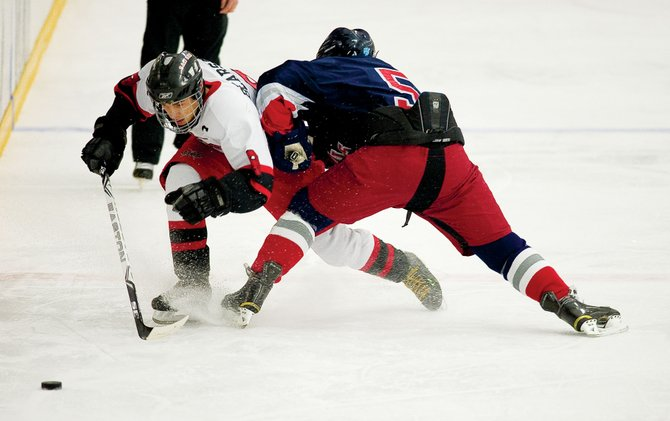 Steamboat Springs center Jake Bearss attempts to get around Kent Denver defender John Eansor during Friday night's game at Howelsen Ice Area.