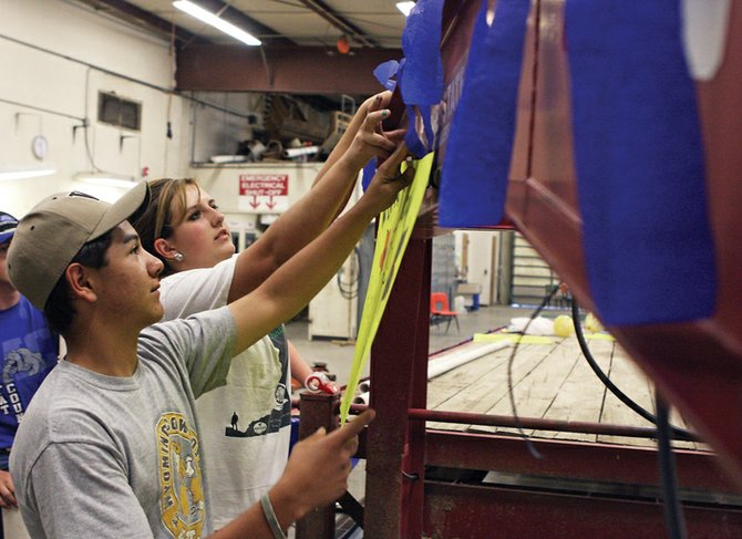 Sophomore Brady Martinez, foreground, and senior Karissa Maneotis work together to hang a sign on the front of the FFA Homecoming float Wednesday in the agriculture shop at Moffat County High School. The Homecoming parade will begin at 2 p.m. today.