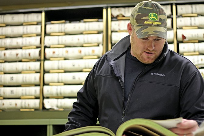 Josh Wycough, 28, of Canton, Texas, looks through a land record book Thursday at the Moffat County Clerk and Recorder's Office. Wycough, who works for Energy West of Denver, is one of about 25 landmen combing through records to find the names of mineral owners in Moffat County.