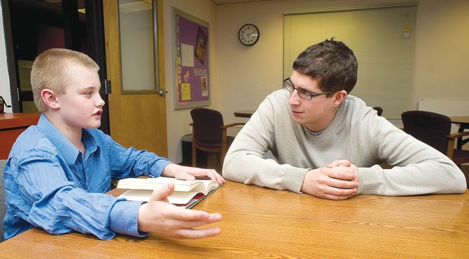 Sixth-grader Gage Reynolds and his school-based mentor Sam Melamed discuss a book that Gage is reading at Steamboat Springs Middle School on Thursday.