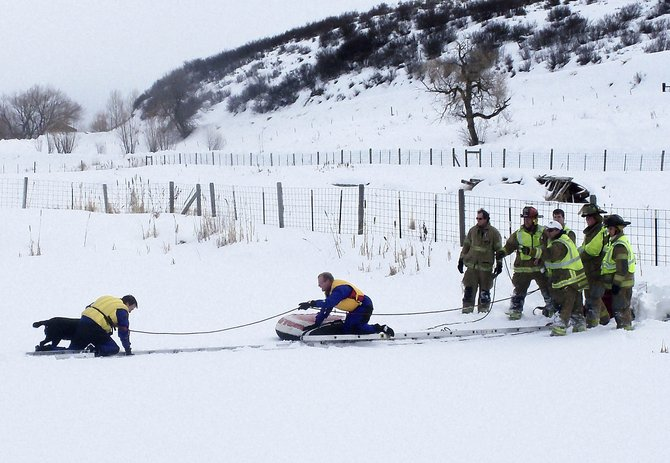 West Routt Fire Protection District firefighters Wayne DeLuca, left, and Dan Parrott, middle, rescue a dog Saturday from a pond along Routt County Road 65 near Hayden.