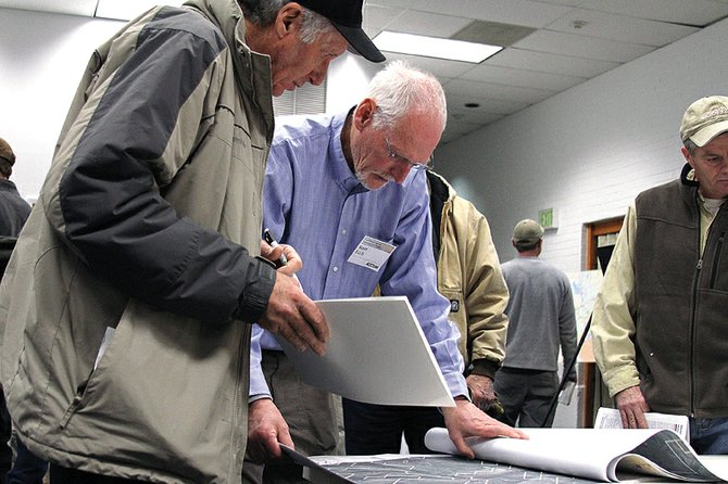 Moffat County resident James Cooper, left, looks Wednesday at maps detailing the proposed and alternative routes of the proposed 600-kilovolt, direct current TransWest Express transmission line, which could run through portions of Moffat County.
