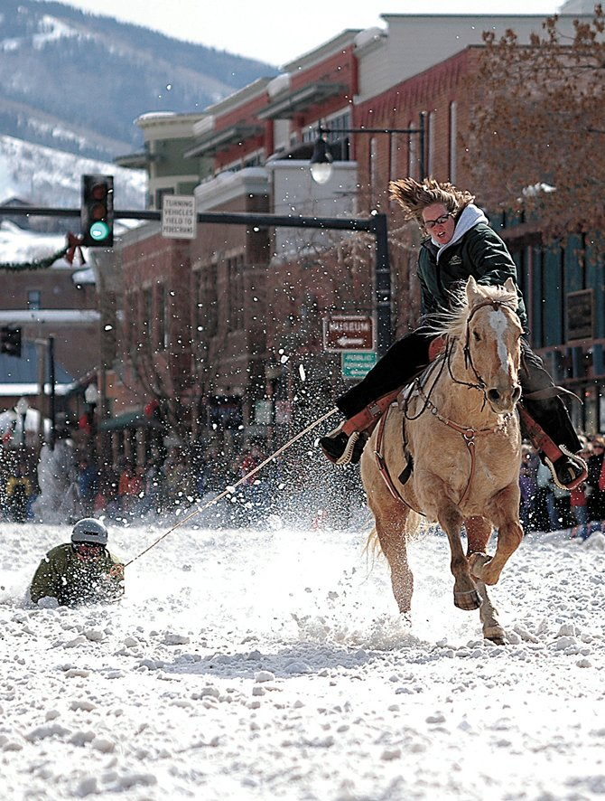 Matt Carter hangs on tight during a shovel race down Lincoln Avenue in 2009. Sheri Yeager is the horseback rider in one of Winter Carnival's most crowd-pleasing events.