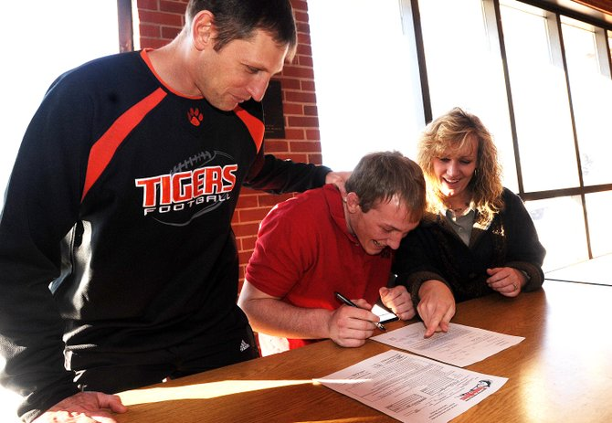 Hayden High School senior Treyben Letlow, with a little help from his mother, Angela, and Tigers football coach Shawn Baumgartner, signs to play football next season for Colorado State University-Pueblo.