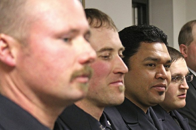 Craig Fire/Rescue academy graduates James St. Louis, Chris Herring, Raul Perez and Tyler McWilliams wait to receive their badges Thursday.