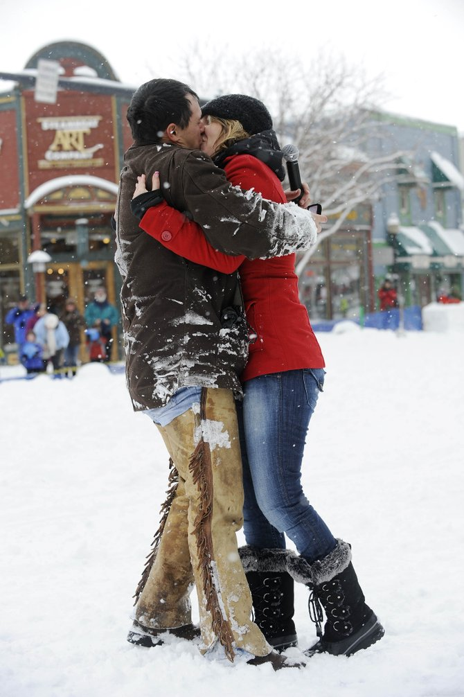 Derrick Jaramillo and Amberly Rin­der­knecht, of Vernal, Utah, kiss after he proposed to her during Saturday's 98th annual Winter Carnival street events in Steamboat Springs.