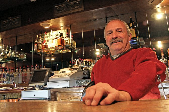 Michael Mathers, 60, stands Thursday in the back bar at Mathers Bar, which he co-owns with his brother, Tom. Michael contracted polio at a young age, but said he doesn't let the affliction hinder his outlook on life. He said he owes much of his continued success to his family.