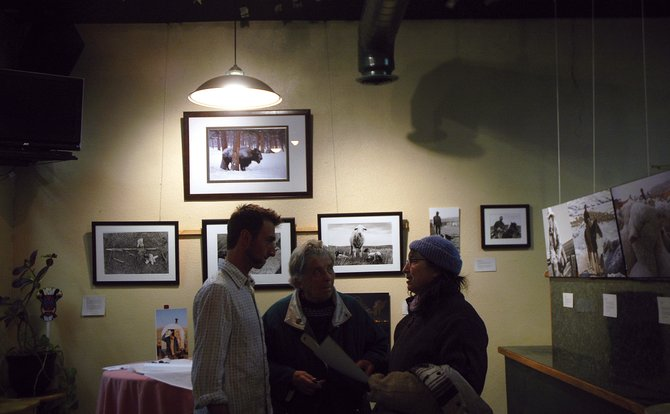 Photographer Yuri Chicovsky, left, discusses his work with Bonnie Villard, center, and Sandy Orgoglioso at Carelli's Pizzeria and Pasta during last year's Art Walk. The 16th annual Art Walk is scheduled for 5 to 8 p.m. Saturday at downtown Craig businesses.