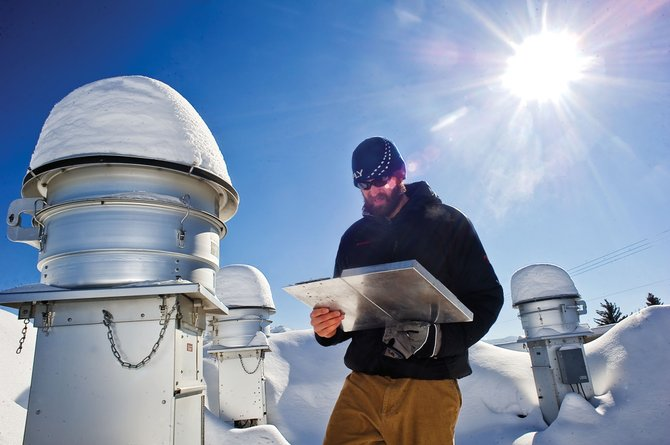 Jason Striker, environmental health specialist for Routt County, checks the air quality monitors on top of the Routt County Courthouse on Wednesday afternoon.