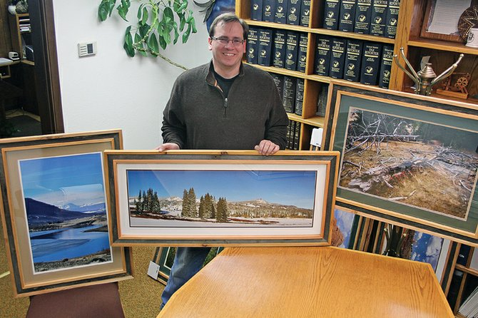 Chad Bonaker, 34, stands with three of his photographs that will be on display at the Rackhouse Pub in Denver for a month-long exhibit. Bonaker first picked up a camera 13 years ago to document his work as a theater lighting designer and had to whittle his collection of 6,000 photos to 30 for his display.