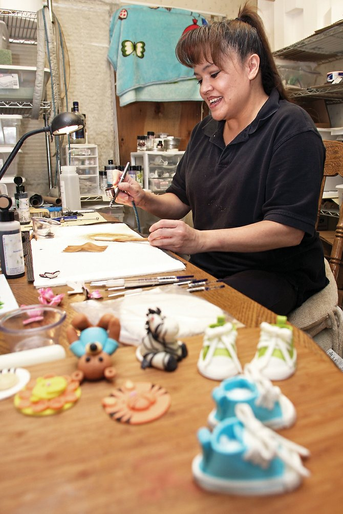 Shirley Cromer airbrushes an edible cake ornament at her home on Legion Street in last April. Cromer's Kahlua Cake Balls were picked as the best item at the 2011 Taste of Chocolate event Saturday. Cromer regularly puts together elaborate cakes despite having no formal training.