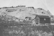 "Pictured is the Van Dorn homestead in August 1918. In the foreground is the Van Dorn house. In the background, is the ""Indian Cave,"" which was dug into the sand rock by the Van Dorns to serve as a chicken coop. The homestead is long gone, but the cave can still be accessed from Tenth Street."