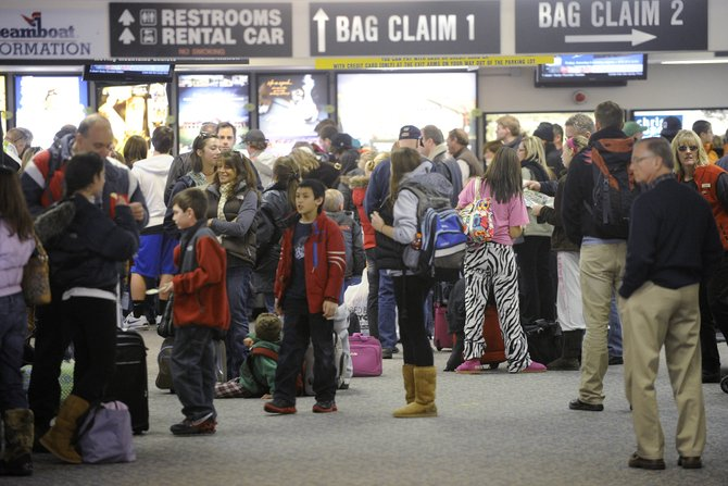 Passengers wait for their baggage Saturday at Yampa Valley Regional Airport. Flights were running on schedule despite a private jet that slid off the runway Friday night.