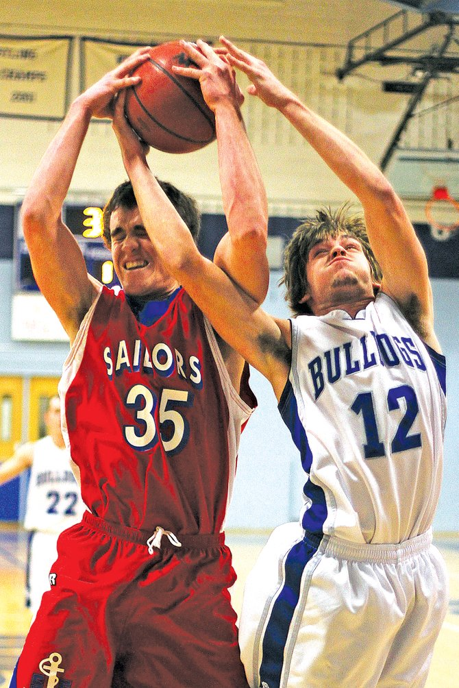 Steamboat's Eric Trousil tries to secure a rebound from Moffat County High School senior Chet Harvey during Friday's game.